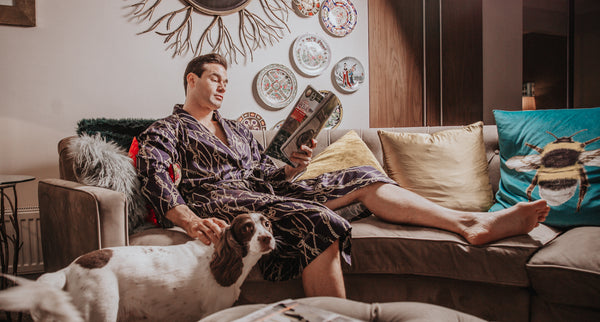 man reading on sofa in dressing gown