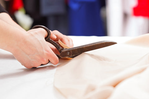 A tailor cutting fabric with sewing shears