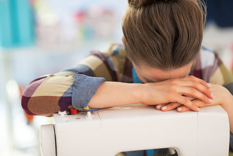 A stressed-out seamstress leaning her head over her sewing machine.
