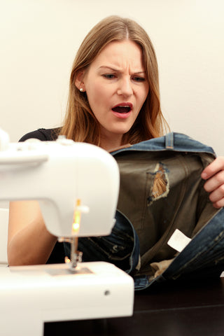 A woman holding a damaged pair of jeans she is sewing and looking shocked.
