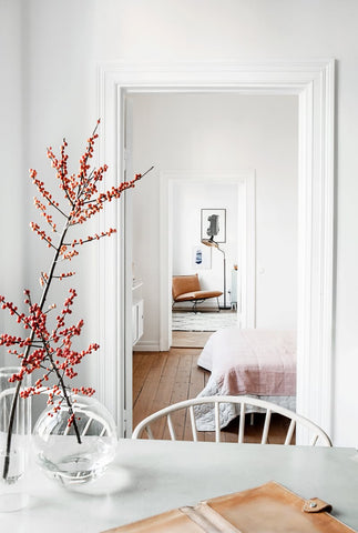 The berry branches red color pops against the neutral colors adding a seasonal and festive element to this home dining area.