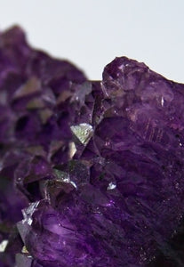 A macro photography of amethyst showing the crystalline structure and inner glow of the purple.