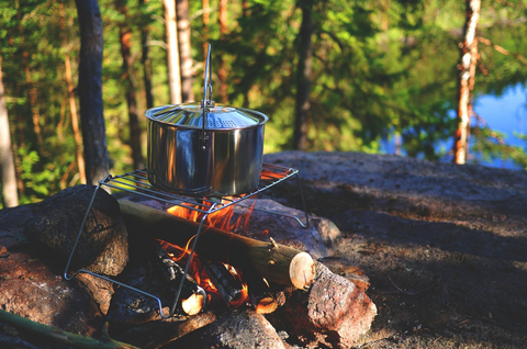 Cooking a pot over wood fire while out camping