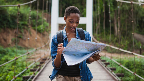 Woman hiking outdoors using a map to plan a route