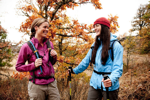 Two women smiling while hiking in nature