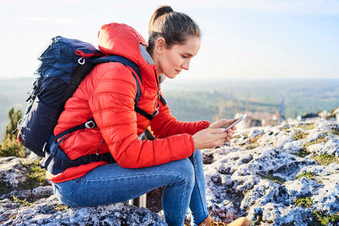 Woman calling a family member or friend to alert them of her hiking location