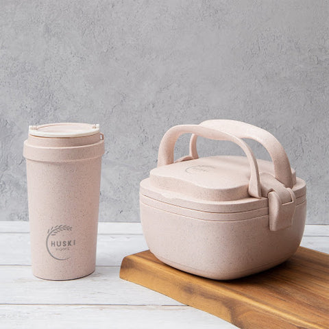 Eco friendly lunchbox and matching takeaway coffee cup in a dusty pink on a wooden chopping board.