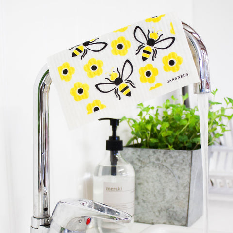 White reusable dishcloth with a bright yellow bee and flower pattern, in a beautiful kitchen
