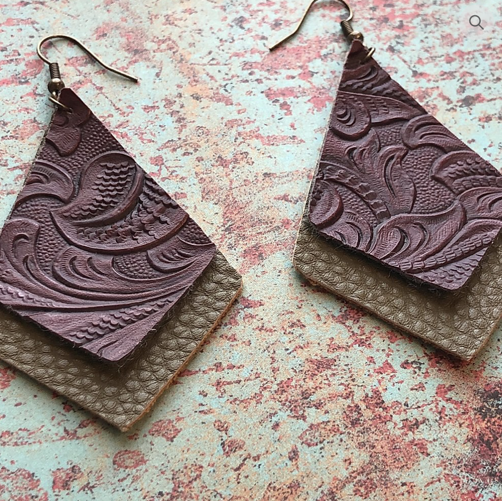 2 layered faux leather pieces both Dimond like shape bottom one larger olive green  color top smaller brown tooled faux leather pattern