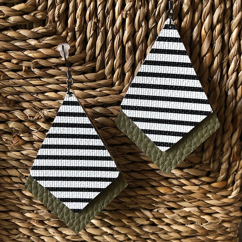 2 layered faux leather pieces both Dimond like shape bottom one larger olive green  color top smaller black and white striped pattern Dimond like shape background wicker basket