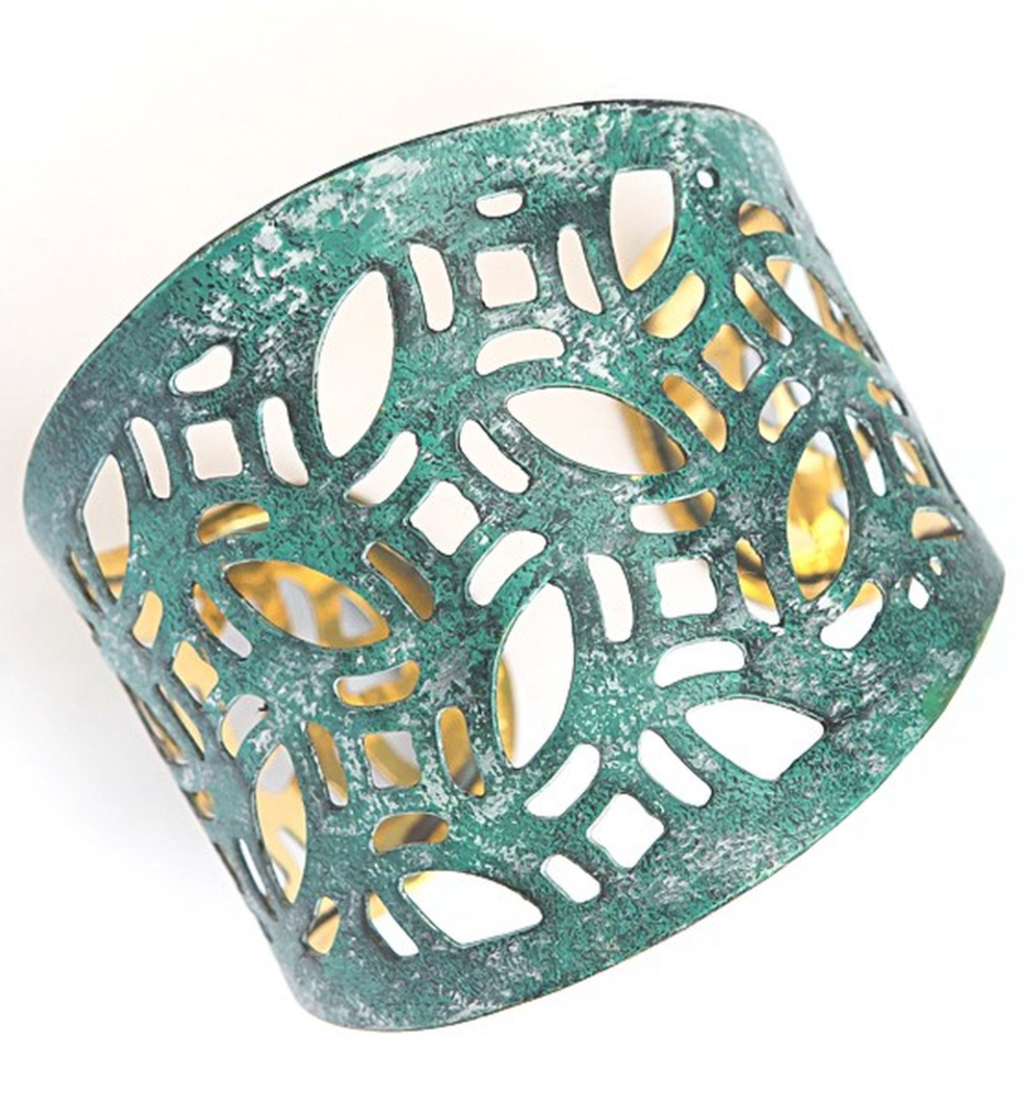 cuff cut into a lace like pattern with many shapes outer color looks like a natural green/blue and white patina inside cuff is a gold like color