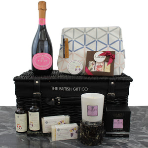 Baby Girl Gift Basket with English sparkling wine, massage oils for mum and new baby, luxury candle and chocolate with a toilet bag.