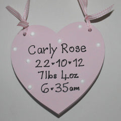 Handpainted wooden heart in pink personalised with babies details and with a ribbon to hang it.