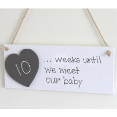 white plaque with countdown until we meet our baby and a chalkboard heart