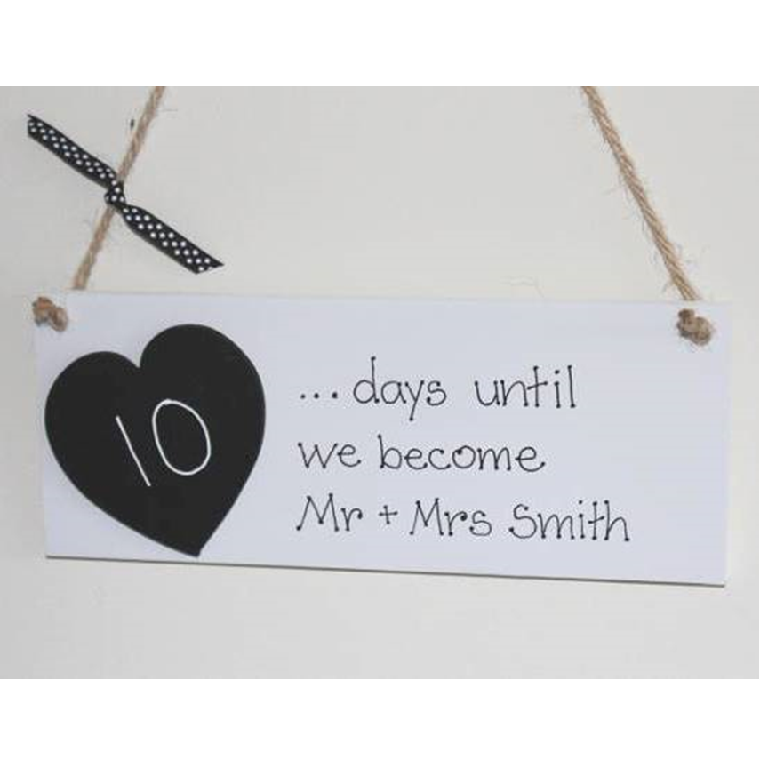 White wooden plaque saying days until we become mr and mrs with a blackboard heart to countdown the days on