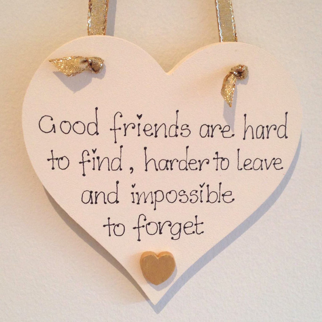Wooden heart painted in white and gold with saying good friends are hard to find