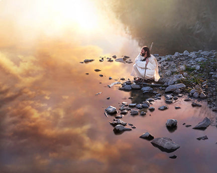 Christ sit on rocky shoreline looking over water filled with reflection of sunset