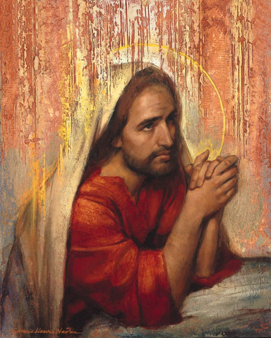 Jesus clothed in red praying against rock in Gethsemane.