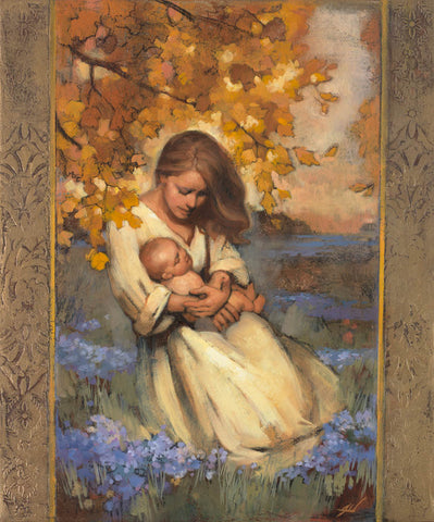 A mother holding and praying for her child surrounded by autumn leaves.