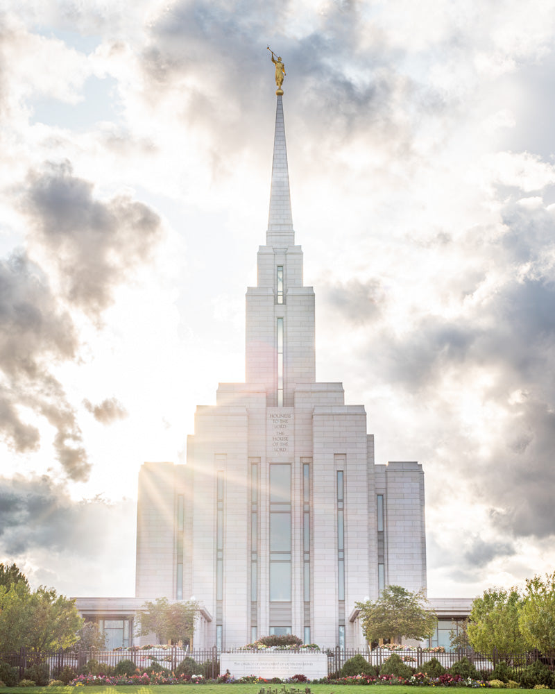 Front View of Oquirrh Mountain Temple with light shining from behind.