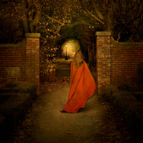 A young woman in a red cloak holds a light as she ventures down a garden path.