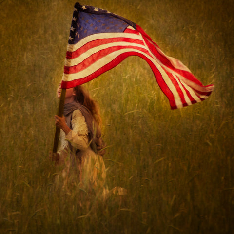 A young girl running through a field waving the American flag.