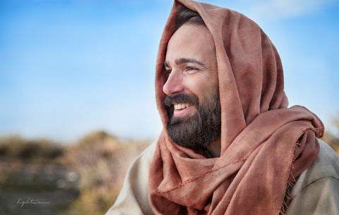 Profile portrait of jesus smiling with red shawl on head.