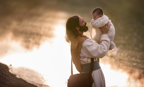 Jesus holding up a baby and smiling.