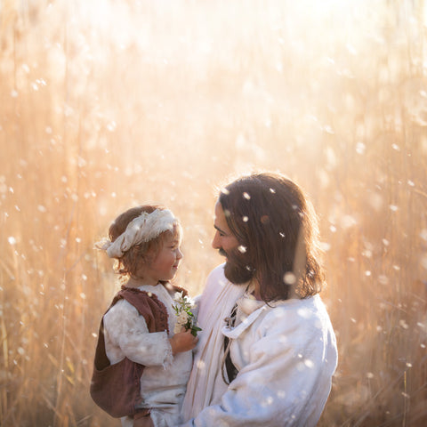 Jesus with a young child holding a flower and smiling.