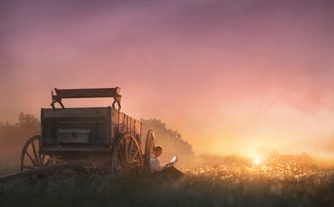 Young Joseph Smith sitting by a wagon reading at sunset.