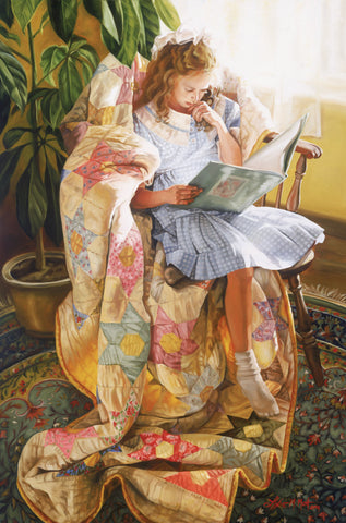 A girl sitting on a quilt in a chair by a window reading.