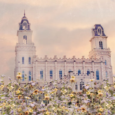 Side view of the Manti Utah Temple with pink and yellow flowers.