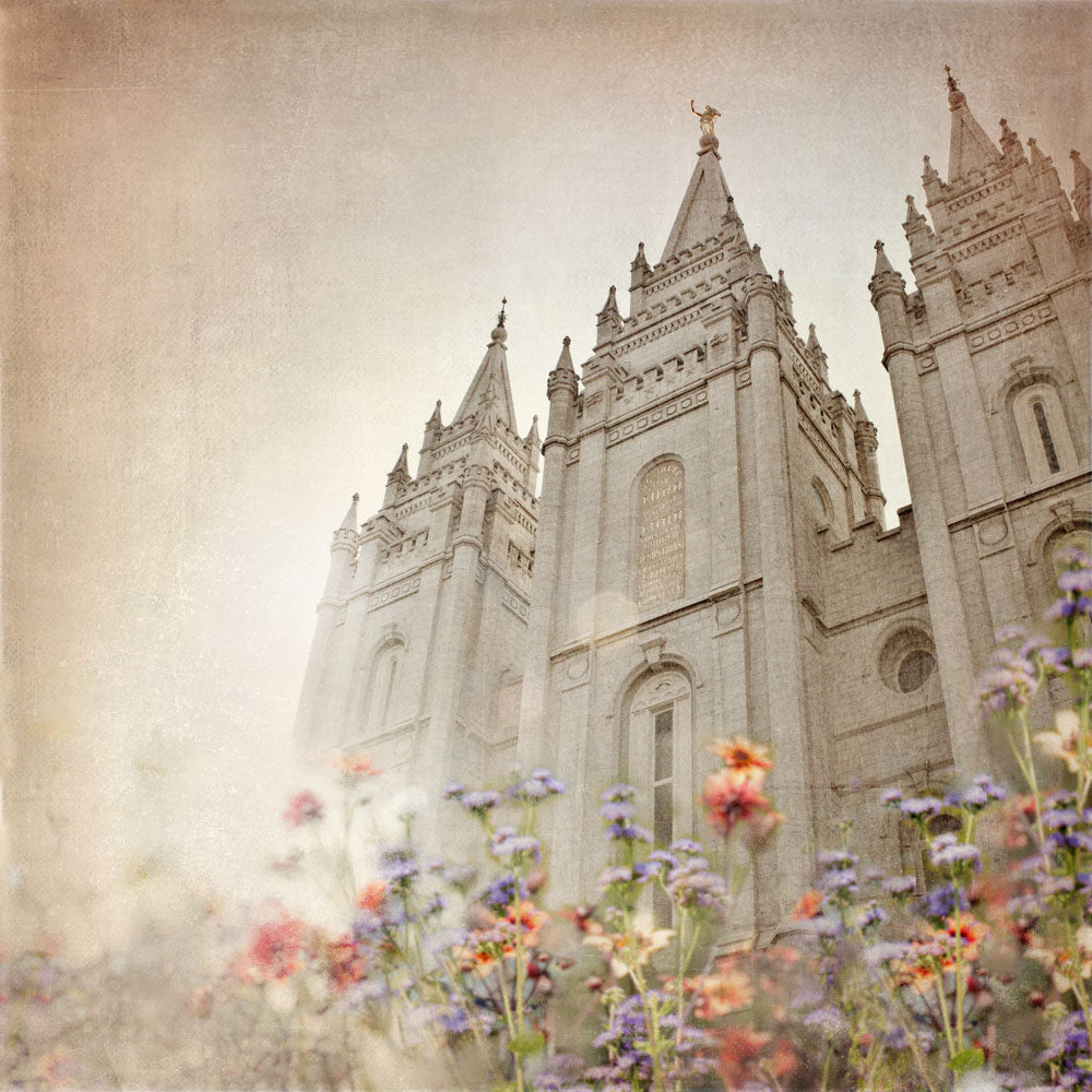Salt Lake Utah Temple with red and purple wild flowers.