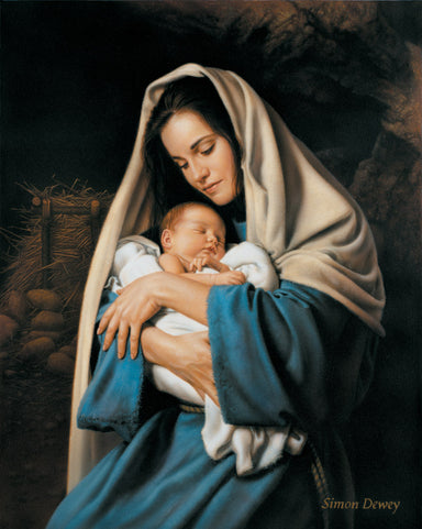 Mary holding baby Jesus in her arms with the manger in the background.