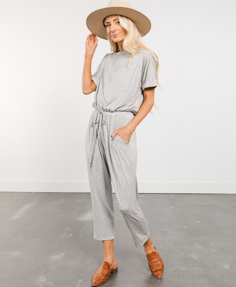 Short sleeve heather grey jumpsuit with pockets and a drawstring waist.