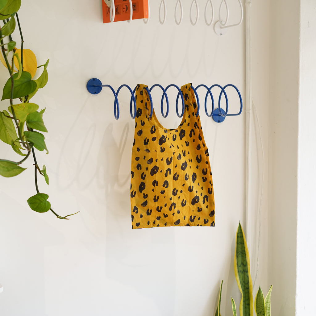 The Baby Baggu in Leopard hanging on the Corkscrew Wall Hook at Commonplace design shop.