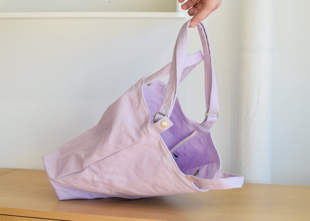 The Baggu Duck Bag in lilac, with adjustable strap.