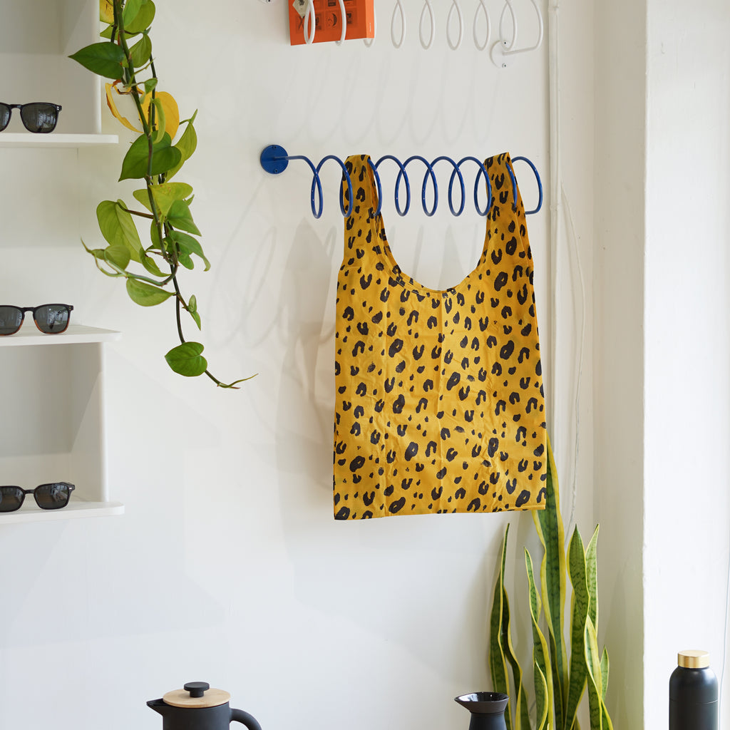 The Standard Baggu in Leopard hanging on the Corkscrew Wall Hook at Commonplace design shop.