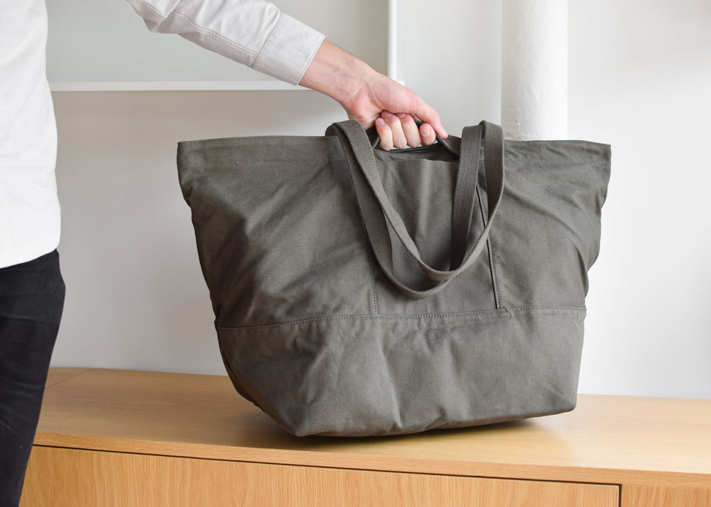 The Weekend Bag in dark olive has two handles on the top, and two longer tote handles.