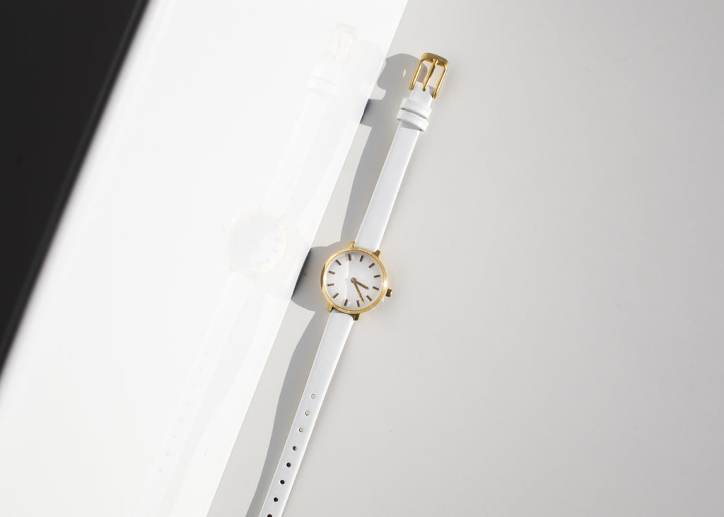 The Beverly Watch in gold & white from Breda features a thin leather band and small face.