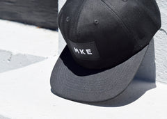 "Milwaukee Hat from Commonplace shown propped up with ""MKE"" logo."