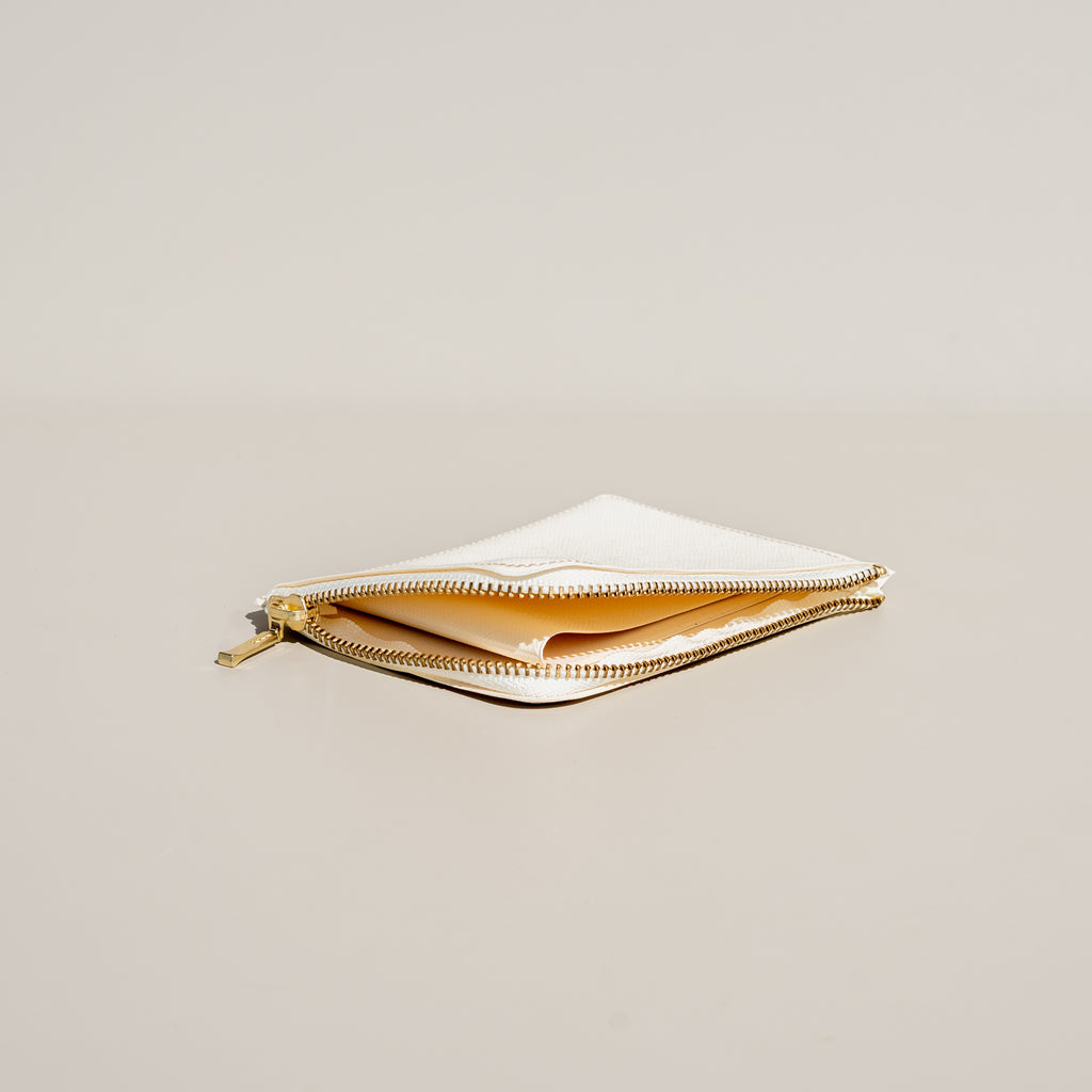 From Delfonics, Quitterie Half-Zip Wallet in cream with interior pocket for cash or cards.