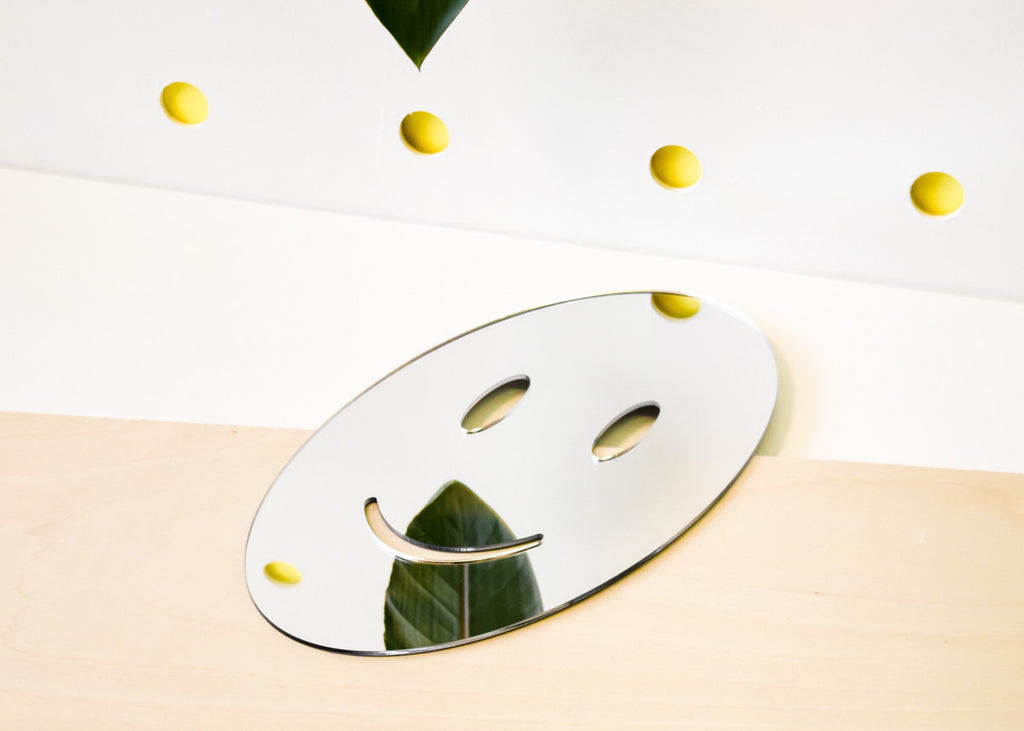 The Smile Emoji Mirror designed by Miguel Ramirez right side up from Commonplace.