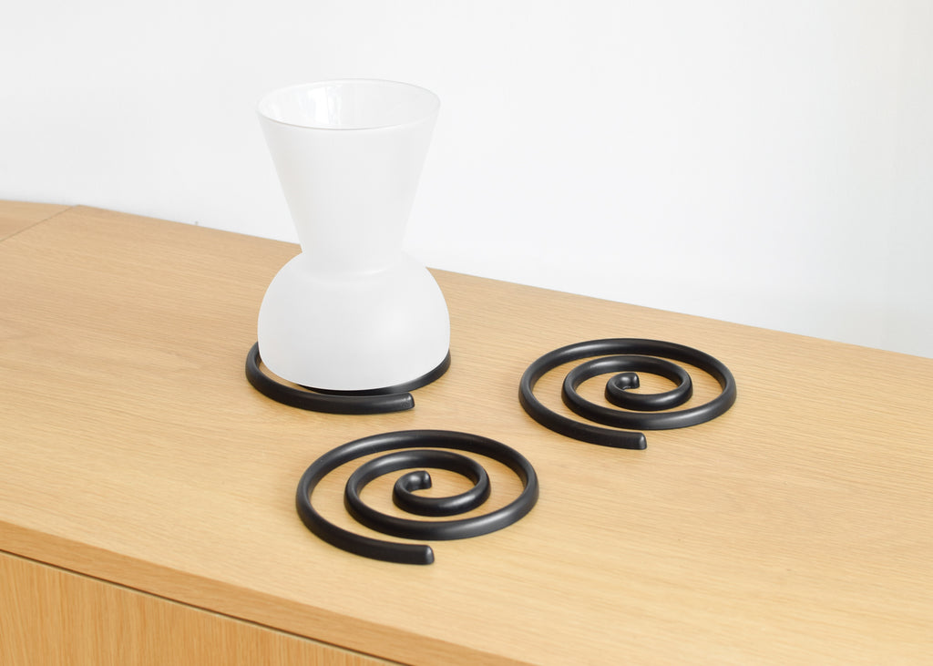 Made of sand cast aluminum, the Good Thing Spiral Trivet set creates a fun table display.
