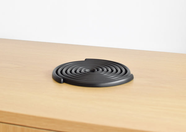 The Good Thing Spiral Trivet Set in black, designed by Sam Anderson & Jamie Wolfond.