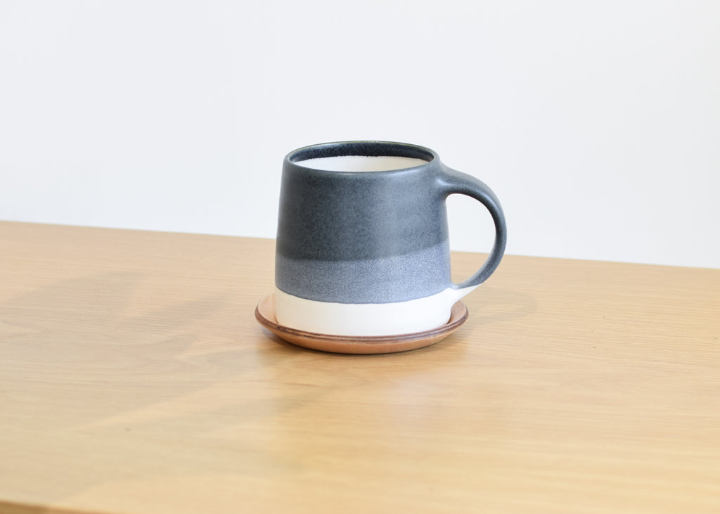 The small wood Cast Coaster by Kinto with coffee mug.