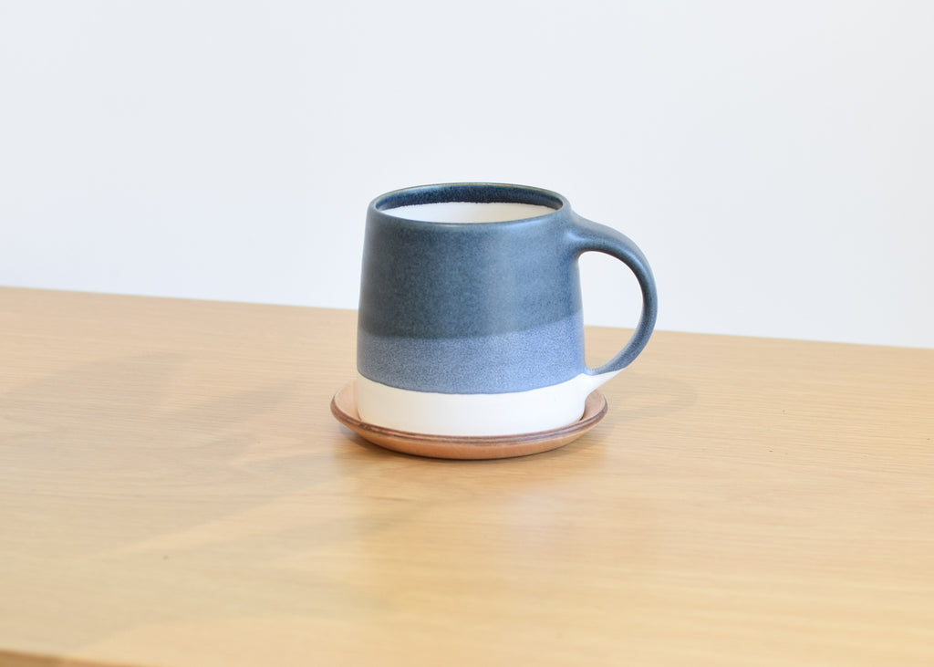 The Slow Coffee Style Mug in navy and white with a Cast Coaster.