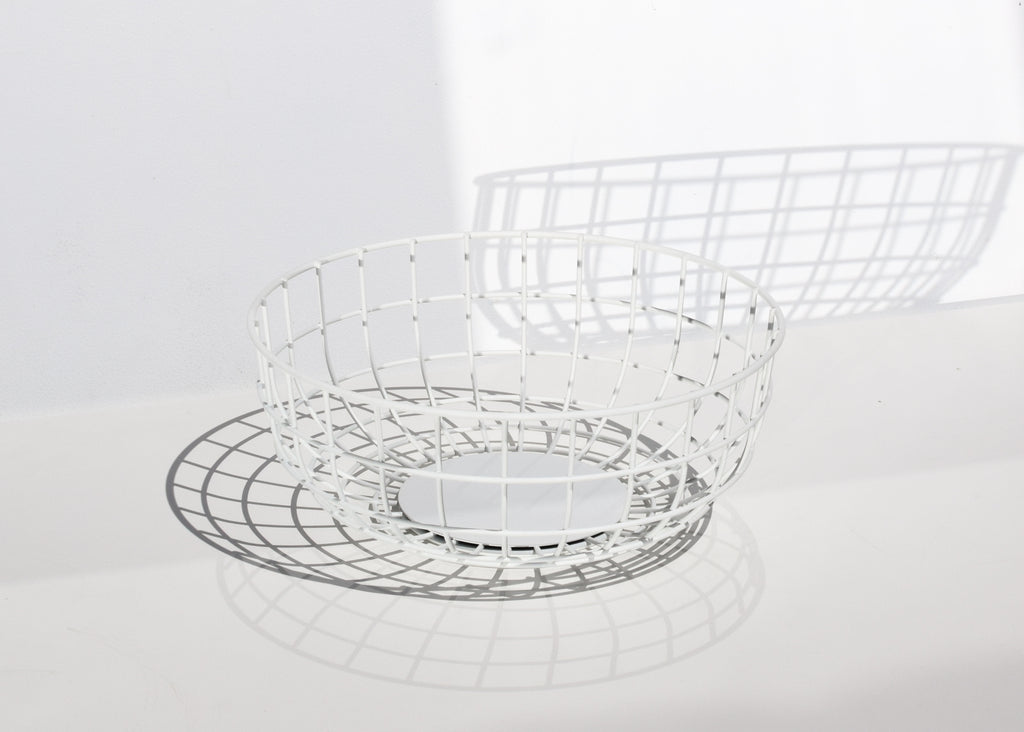 Menu Wire Bowl in white, with strong geometric shadows.