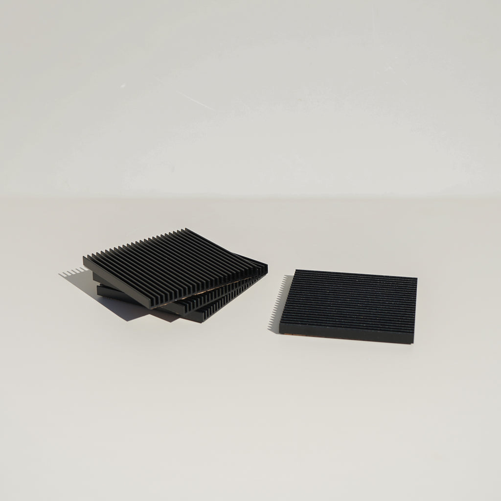 The Fin Coasters in black by Souda, designed by Shaun Kasperbauer.