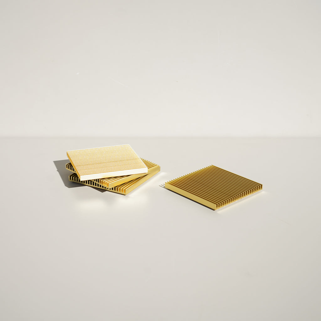 The Fin Coasters in gold by Souda, designed by Shaun Kasperbauer.
